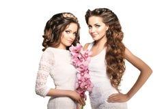Två unga kvinnor för skönhet, lyxigt långt lockigt hår med orkidéflowe Royaltyfri Bild