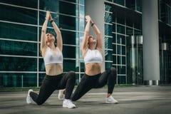Två unga kvinnor, flickor som gör sträcka övningar, uppvärmning som gör yoga på stadsgatan Genomkörare som uttrycker på stadsgata arkivbild