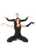 Två unga kvinnor gör elasticitet på yoga att posera Fotografering för Bildbyråer
