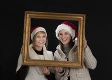 Två unga kvinnor i en inrama, på svart Royaltyfria Foton