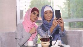 Två unga kvinnor i hijabs gör selfie på en smartphone Muslimska kvinnor i ett kafé Royaltyfri Foto