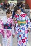 Två unga kvinnor i kimonot som ser mobiltelefonen på den Sensoji knoppen Royaltyfri Bild