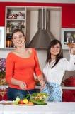 Två unga kvinnor i modernt kök Arkivbilder