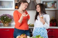 Två unga kvinnor i modernt kök Arkivfoto