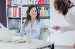 Två unga kvinnor i regeringsställning som tillsammans arbetar på skrivbordet Royaltyfri Foto