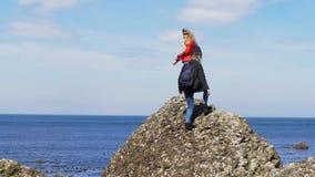 Två unga kvinnor klättrar på vaggar av jättevägbanken i nordligt - Irland lager videofilmer