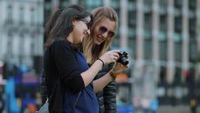 Två unga kvinnor kontrollerar foto på kameran - den London sighten arkivfilmer