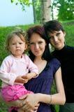 Två unga kvinnor med ett litet barn Arkivbild