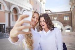 Två unga kvinnor med shoppingpåsar som tar en selfie Royaltyfri Foto