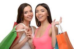 Två unga kvinnor, når att ha shoppat med påsar Royaltyfria Foton