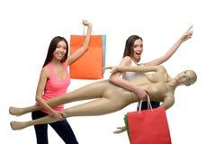 Två unga kvinnor, når shoppa med påsar och Fotografering för Bildbyråer