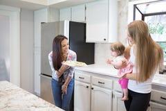 Två unga kvinnor och liten flicka i köket Royaltyfria Bilder