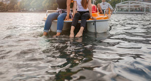 Två unga kvinnor på ett pedalofartyg med fot i vatten Royaltyfri Bild