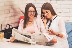 Två unga kvinnor söker efter ett jobb i tidningen arkivbilder