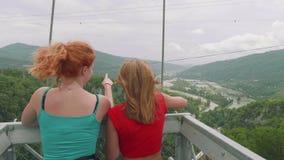 Två unga kvinnor ser den gröna den bergdalen och turisten på spårvagnen i berg arkivfilmer