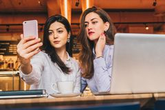Två unga kvinnor sitter i ett kafé på en tabell framme av en bärbar dator och gör selfie på en smartphone Möte av två vänner fotografering för bildbyråer