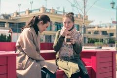 Två unga kvinnor sitter på en ljus rosa färgbänk och dricker kaffe i koppar och att tycka om det soliga vädret och skumet från ka Royaltyfria Foton