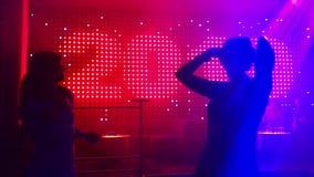 Två unga kvinnor som dansar på dansgolvet i nattklubb arkivfilmer