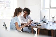 Två unga kvinnor som diskuterar dokument på ett skrivbord i ett kontor arkivfoto