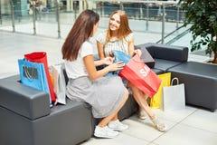 Två unga kvinnor som diskuterar Sale Royaltyfri Bild