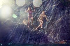 Två unga kvinnor som dyker från en klippa i havet Arkivbild