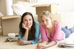 Två unga kvinnor som flyttar sig in i det nya hemmet som packar upp askar Arkivfoto