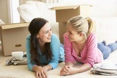 Två unga kvinnor som flyttar sig in i det nya hemmet som packar upp askar Fotografering för Bildbyråer