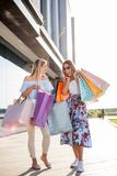 Två unga kvinnor som framme bär shoppingpåsar av en galleria royaltyfria foton