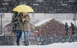 Två unga kvinnor som går under paraplyet i tungt snöfall i stadsgata arkivbild