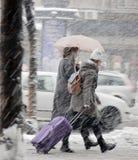Två unga kvinnor som går under paraplyet i tungt snöfall i stadsgata arkivfoto