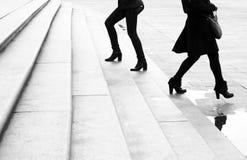 Två unga kvinnor som går uppåt- och neråt enormt flytta sig för stadstrappa royaltyfri bild