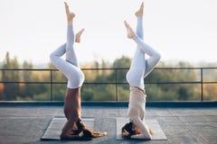 Två unga kvinnor som gör dubbel yogaasana, stöttade huvudstående Arkivbild