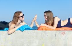 Två unga kvinnor som hälsar gest för höjdpunkt fem Royaltyfria Bilder