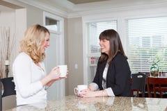 Två unga kvinnor som har ett skratt över kaffe Royaltyfria Bilder