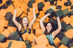 Två unga kvinnor som har gyckel med mjuka kvarter på inomhus barn p royaltyfria bilder