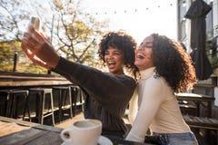 Två unga kvinnor som har gyckel som tar en selfie Royaltyfria Bilder