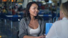 Två unga kvinnor som har kaffeavbrottet, når att ha shoppat i galleria Arkivfoton