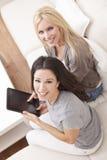 Två unga kvinnor som hemma använder Tabletdatoren Arkivbilder