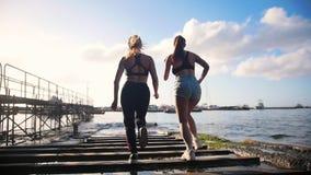 Två unga kvinnor som joggar på, vaggar havet en port in mot för havet - i Sorrento, Italien arkivfilmer