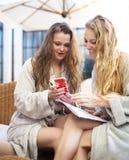 Två unga kvinnor som kopplar av i den bärande toweling ämbetsdräkten för brunnsortsemesterort Arkivfoto