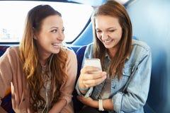 Två unga kvinnor som läser textmeddelandet på bussen Arkivfoton