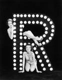 Två unga kvinnor som poserar med bokstaven R (alla visade personer inte är längre uppehälle, och inget gods finns Leverantörgaran Royaltyfri Foto