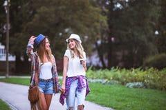 Två unga kvinnor som rymmer händer som går i gräsplan, parkerar Bästa vän arkivbild