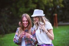 Två unga kvinnor som rymmer händer som går i gräsplan, parkerar Bästa vän arkivfoton