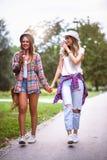 Två unga kvinnor som rymmer händer som går i gräsplan, parkerar Bästa vän arkivfoto