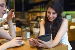 Två unga kvinnor som ser en digital minnestavla Royaltyfria Bilder