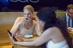 Två unga kvinnor som ser en digital minnestavla Royaltyfria Foton