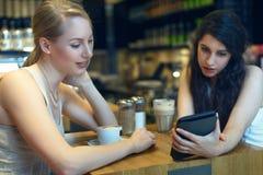 Två unga kvinnor som ser en digital minnestavla Royaltyfri Bild
