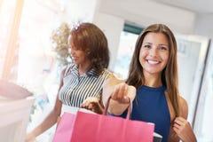 Två unga kvinnor som shoppar i en boutique Royaltyfria Bilder