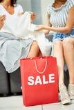 Två unga kvinnor som shoppar på Sale Arkivfoton
